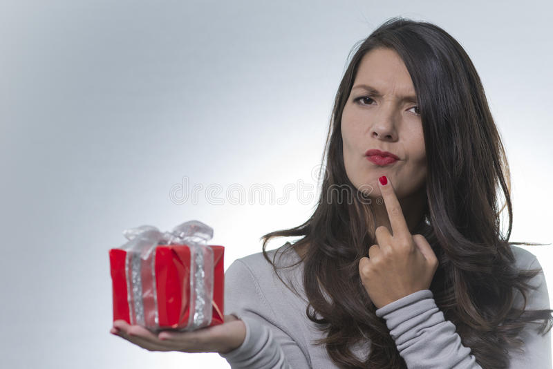 Mujer que mira un regalo con una mirada desconcertada imagen de archivo libre de regalías