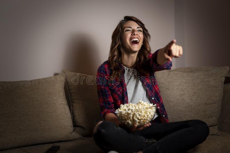 Mujer que mira una comedia en la TV imagen de archivo