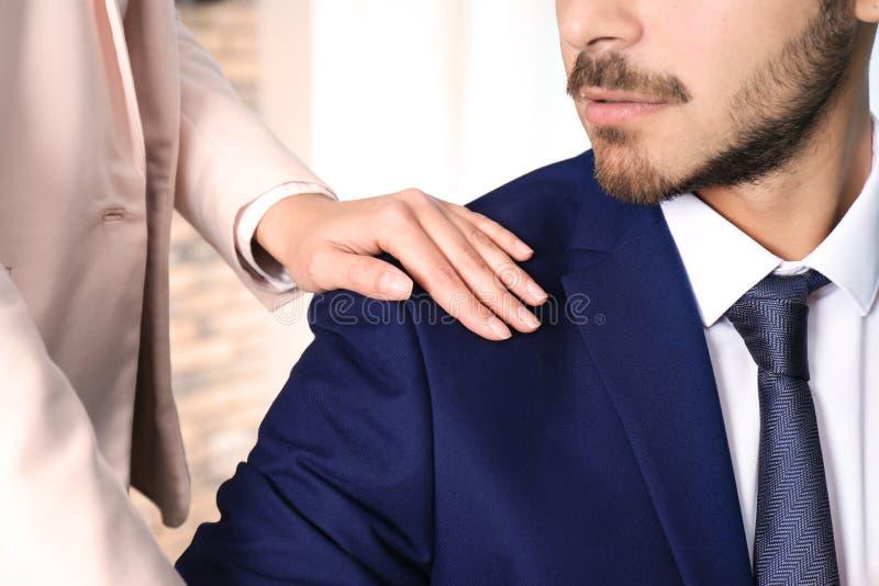 Mujer que molesta a su colega masculino en la oficina, primer foto de archivo