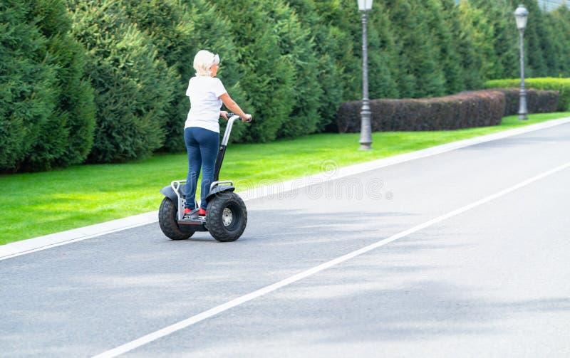 Mujer que monta el largo camino personal del transportador abajo fotos de archivo