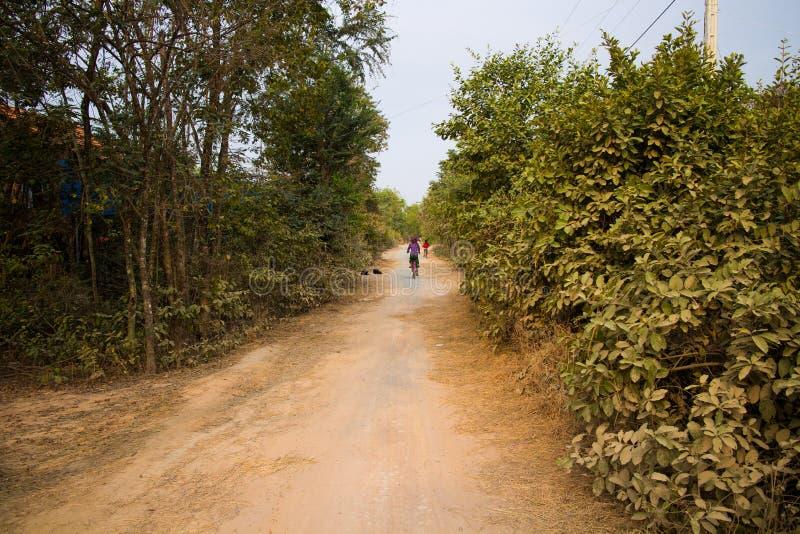 Mujer que monta en bicicleta en un camino en los perros rurales de Camboya Asia fotografía de archivo libre de regalías