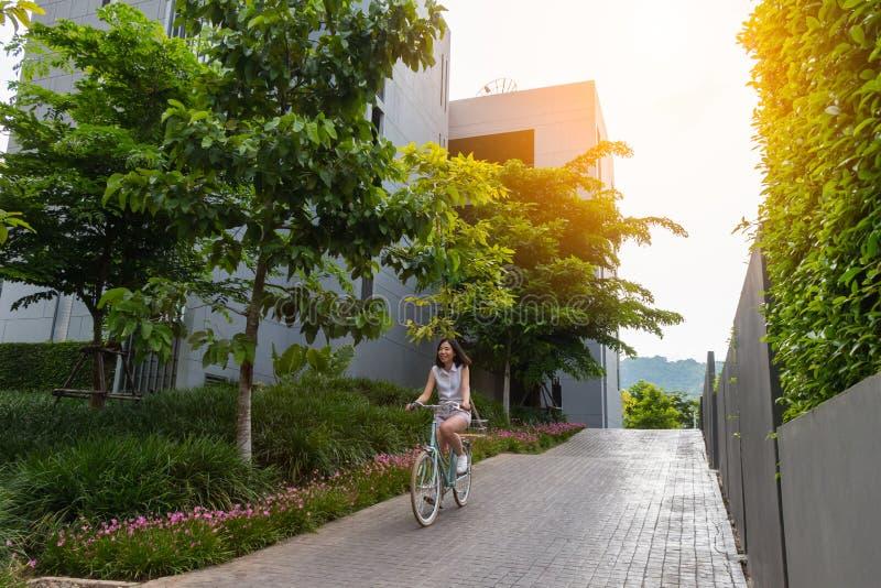 Mujer que monta la bicicleta con luz del sol fotografía de archivo libre de regalías