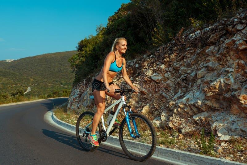 Mujer que monta una bici en un camino de la montaña imagen de archivo libre de regalías