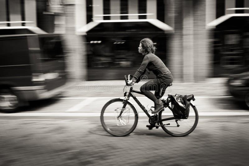 Mujer que monta una bicicleta abajo de la calle. Amsterdam imágenes de archivo libres de regalías