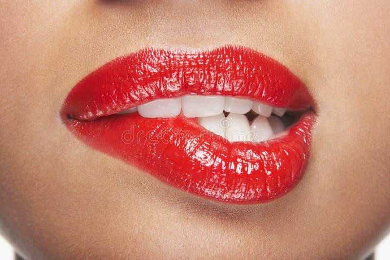Mujer que muerde los labios rojos fotos de archivo libres de regalías