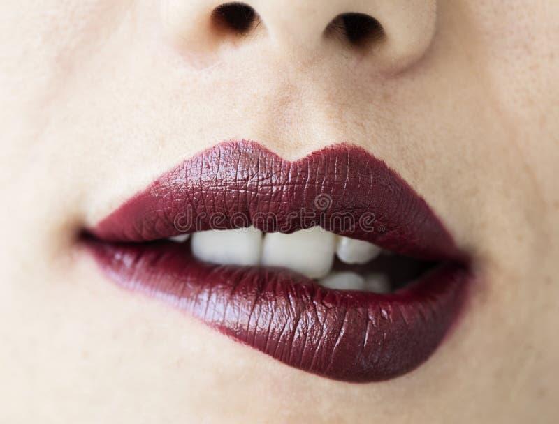 Mujer que muerde sus labios cerca encima de la visión imagen de archivo