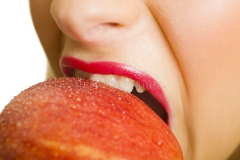 Mujer que muerde una manzana roja fresca foto de archivo libre de regalías