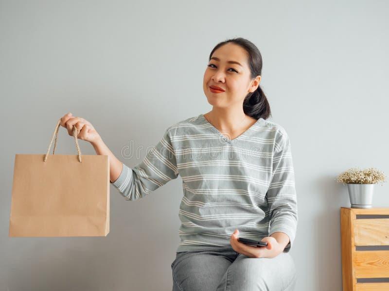 Mujer que muestra apagado la bolsa de papel vac?a del producto que ella compr? en l?nea Concepto de compras en l?nea imagenes de archivo