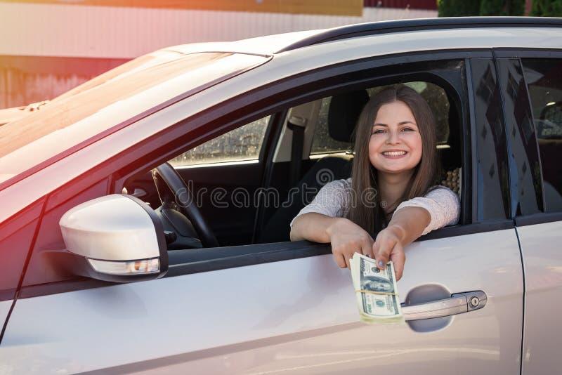 Mujer que muestra dólares y llave de la ventanilla del coche foto de archivo