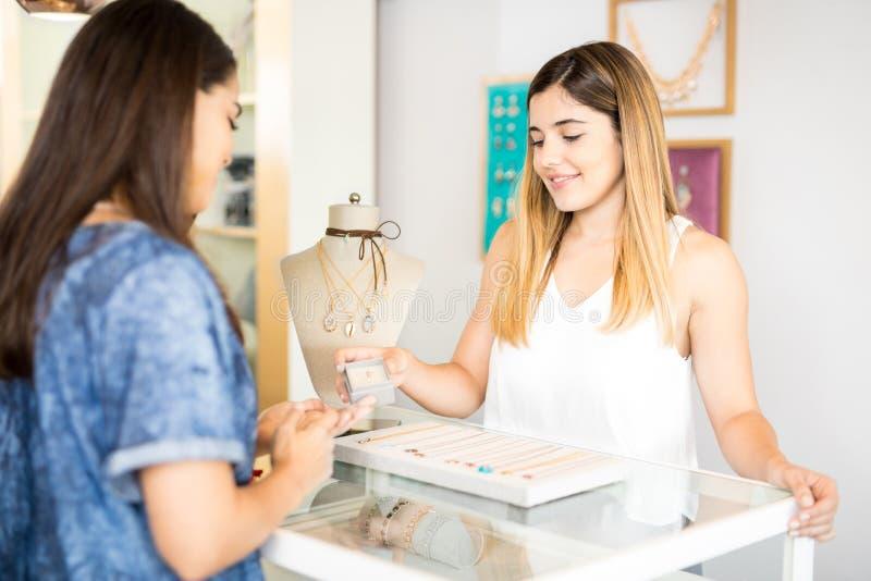 Mujer que muestra el anillo a un cliente fotografía de archivo