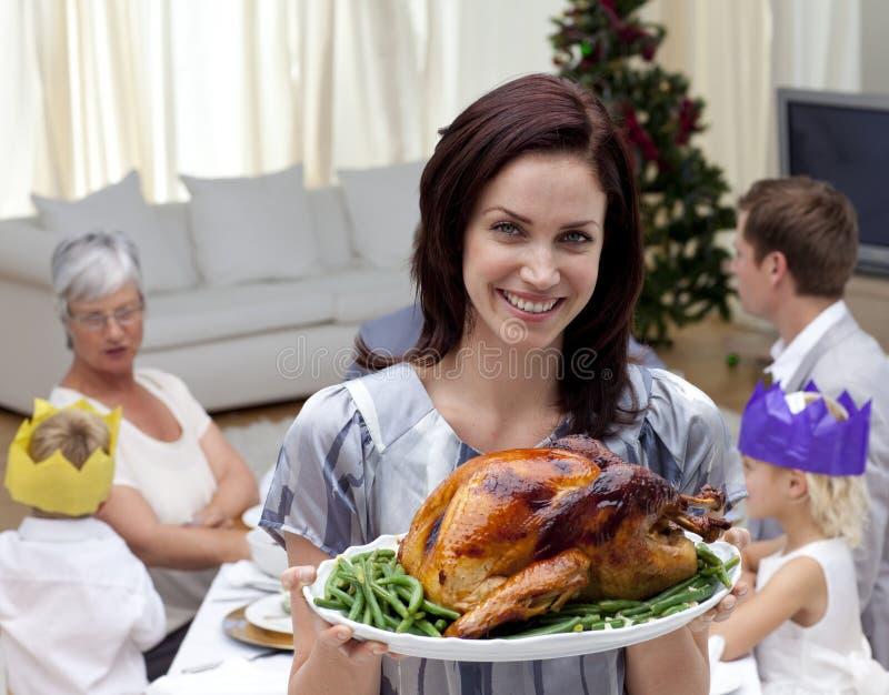 Mujer que muestra el pavo de la Navidad para la cena de la familia