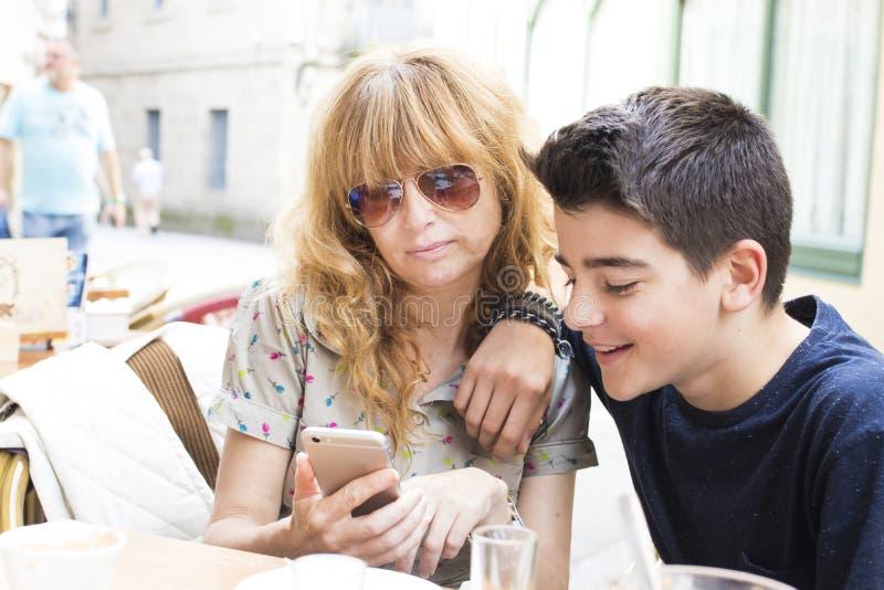 Mujer que muestra el teléfono al muchacho fotografía de archivo
