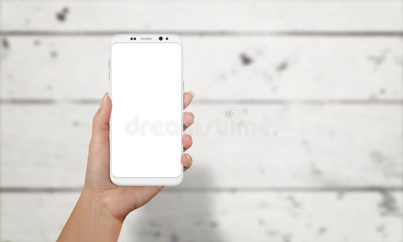 Mujer que muestra el teléfono elegante con los bordes redondos Teléfono de Moder con la pantalla aislada para la maqueta fotos de archivo libres de regalías