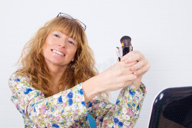 Mujer que muestra influencia en los cosméticos fotografía de archivo