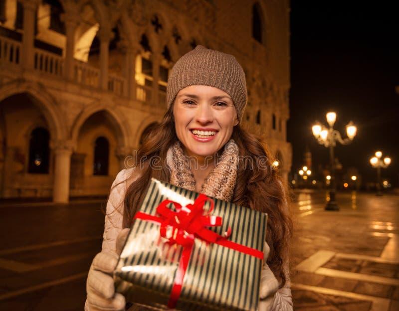 Mujer que muestra la caja de regalo de la Navidad en la plaza San Marco, Venecia foto de archivo libre de regalías