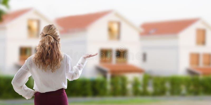 Mujer que muestra la casa en venta foto de archivo libre de regalías