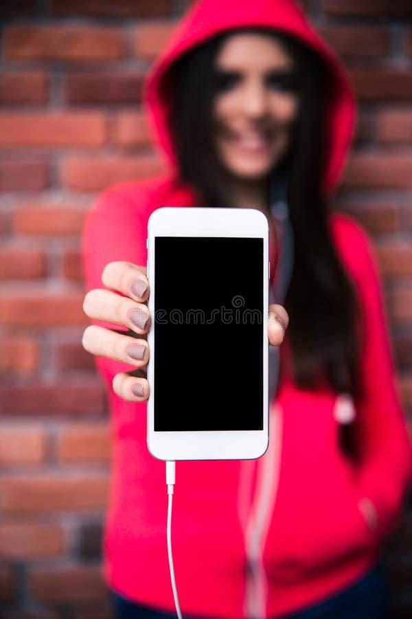 Mujer que muestra la exhibición en blanco del smartphone imagen de archivo