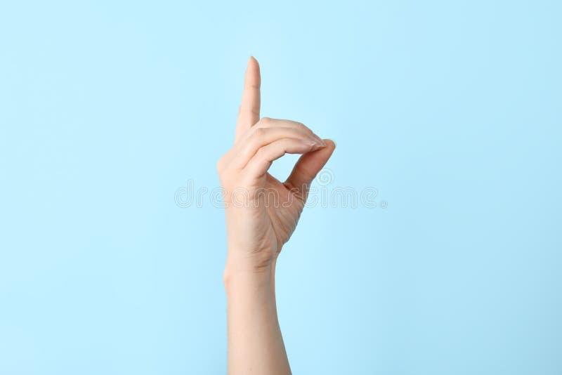 Mujer que muestra la letra de D en fondo del color Lenguaje de signos imágenes de archivo libres de regalías