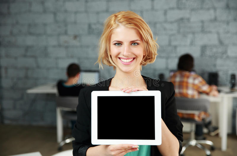 Mujer que muestra la pantalla de tableta en blanco imagen de archivo