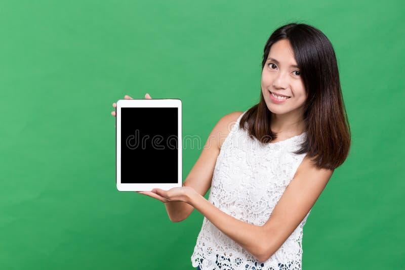 Mujer que muestra la pantalla en blanco de la tableta fotos de archivo