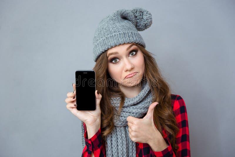 Mujer que muestra la pantalla y el pulgar en blanco del smartphone para arriba imágenes de archivo libres de regalías