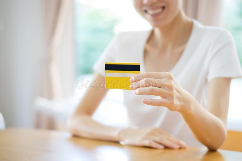 Mujer que muestra la tarjeta del crédito en blanco Foco en tarjeta foto de archivo libre de regalías