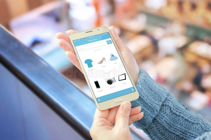 Mujer que muestra la tienda en línea app en el teléfono móvil fotografía de archivo libre de regalías