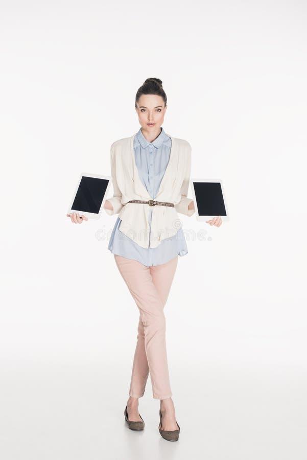 mujer que muestra las tabletas con las pantallas en blanco en manos fotografía de archivo libre de regalías