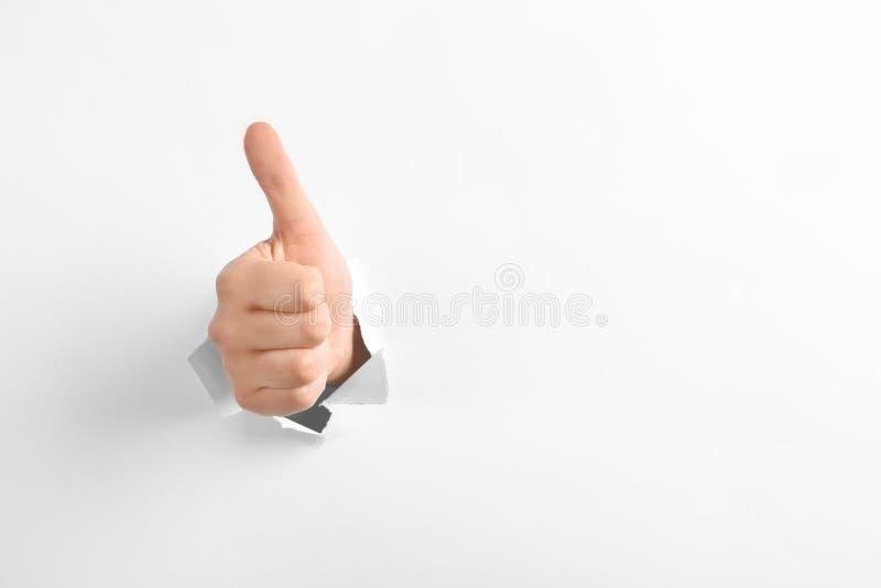 Mujer que muestra los pulgares encima del gesto a través del agujero en el Libro Blanco rasgado, espacio para el texto foto de archivo libre de regalías