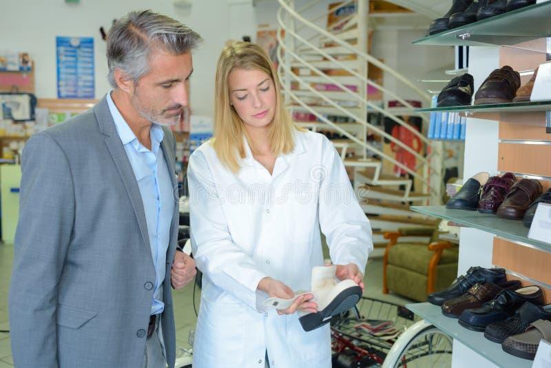 Mujer que muestra los zapatos al cliente imagen de archivo