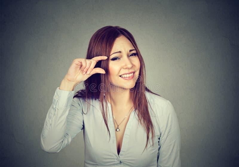 Mujer que muestra pequeña cantidad del gesto del tamaño con los fingeres imágenes de archivo libres de regalías