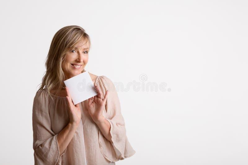 Mujer que muestra sosteniendo la tarjeta en blanco, nota, mensaje fotos de archivo libres de regalías