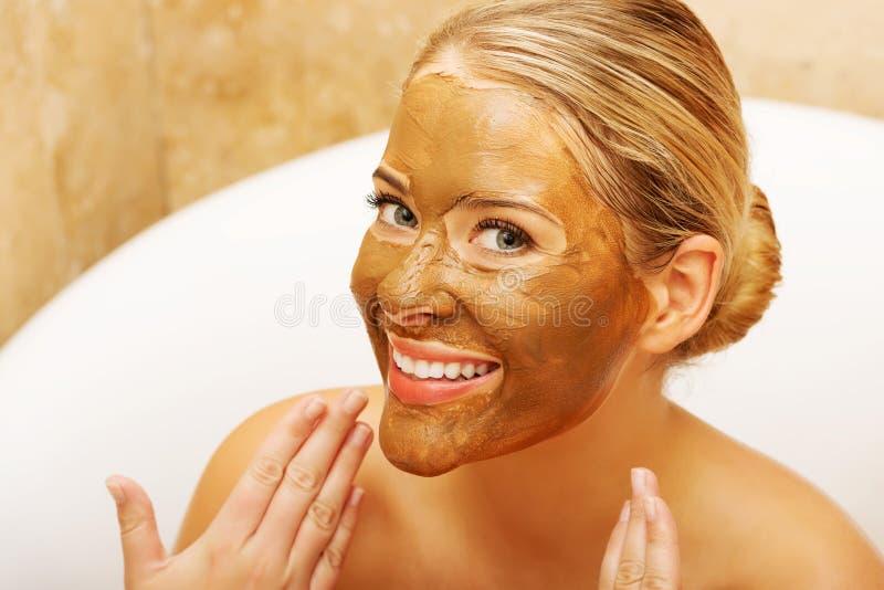 Mujer que muestra su cara con la máscara del chocolate imagenes de archivo