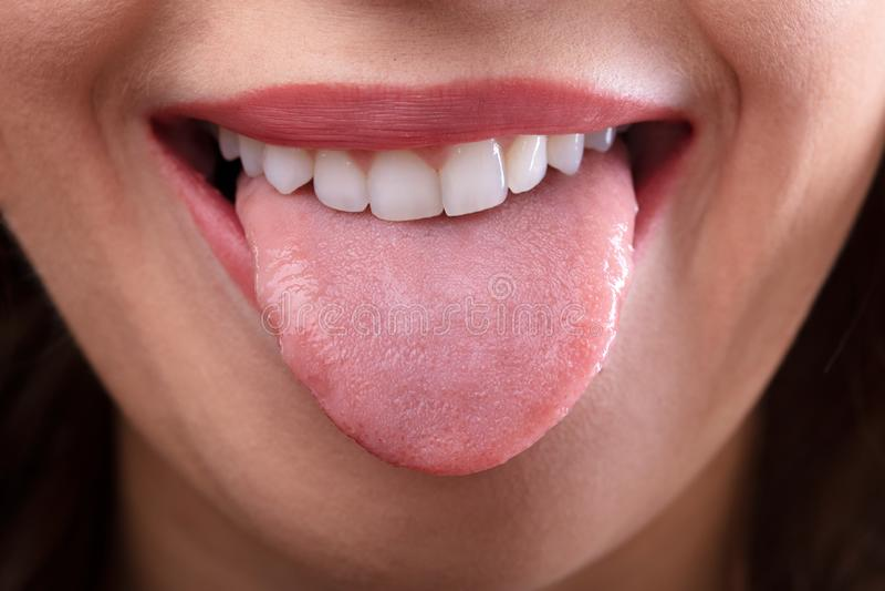 Mujer que muestra su lengua foto de archivo
