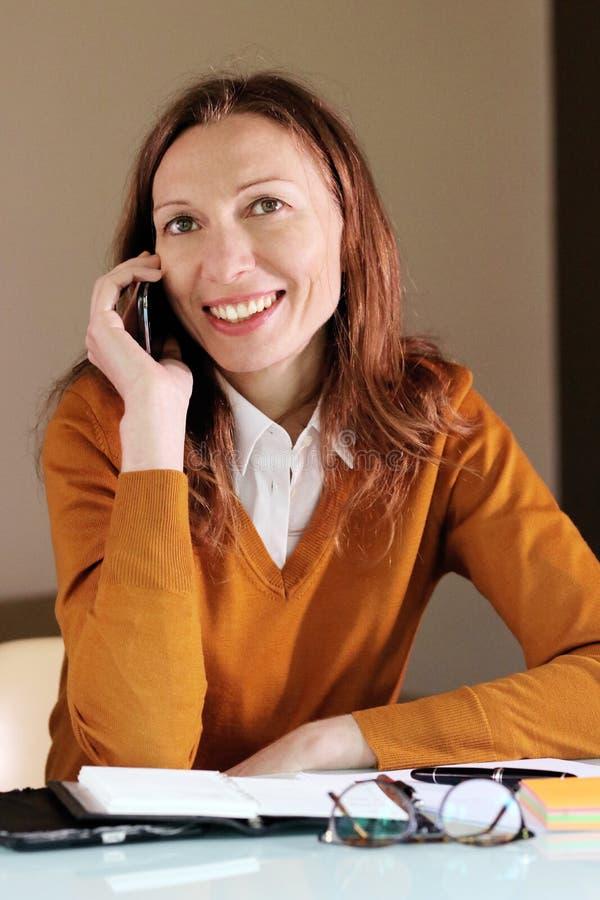 Mujer que negocia con el cliente sobre el teléfono fotos de archivo