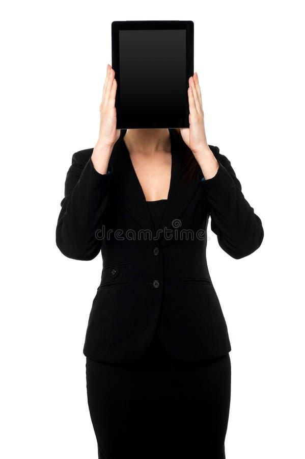 Mujer que oculta su cara con PC de la tableta imagenes de archivo