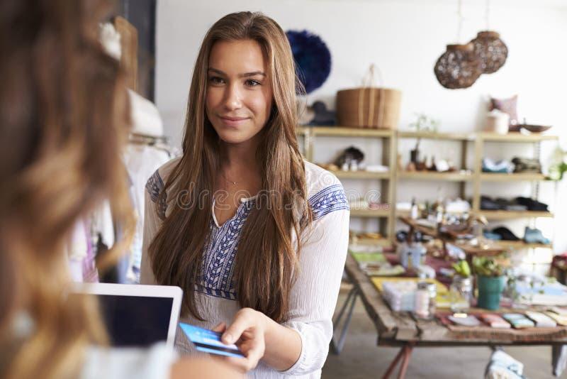 Mujer que paga al ayudante de tienda con la tarjeta de crédito en un boutique foto de archivo libre de regalías