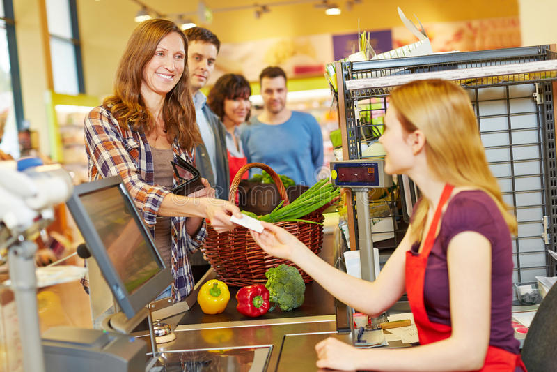 Mujer que paga con la tarjeta de la EC en el pago y envío del supermercado imagen de archivo libre de regalías