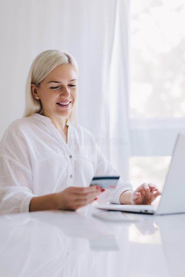 Mujer que paga con su tarjeta de crédito compras en línea fotos de archivo