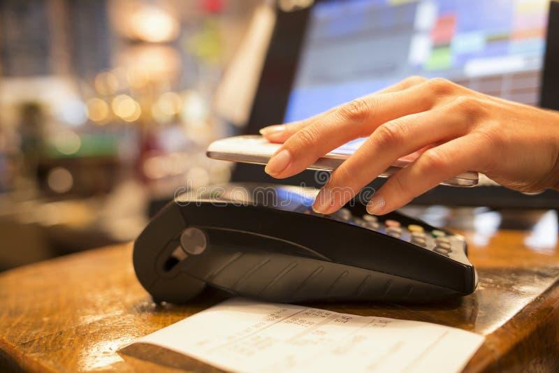 Mujer que paga con tecnología de NFC en el teléfono móvil, restaurante, Ca foto de archivo libre de regalías