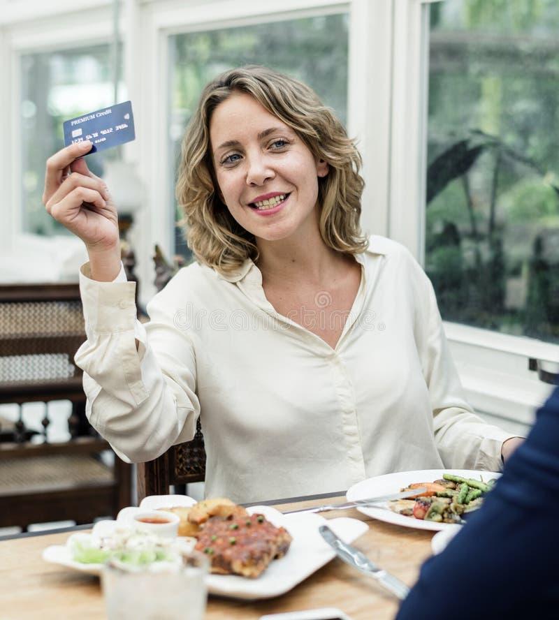 Mujer que paga el almuerzo con la tarjeta de crédito en el restaurante fotografía de archivo libre de regalías