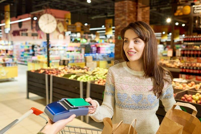 Mujer que paga vía Smartphone en colmado imagen de archivo