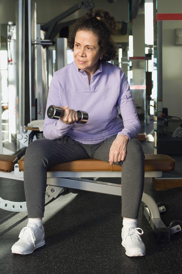 Mujer que parece ausente mientras que levanta el peso en club fotos de archivo