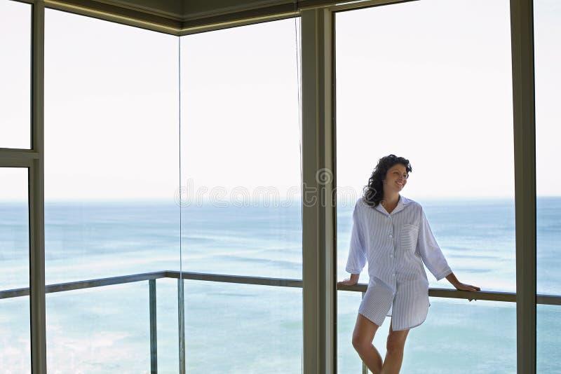 Mujer que parece ausente mientras que se inclina en cercar con barandilla en balcón imagenes de archivo