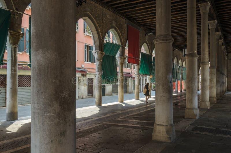 Mujer que pasa a través de arcos en Venecia imagenes de archivo