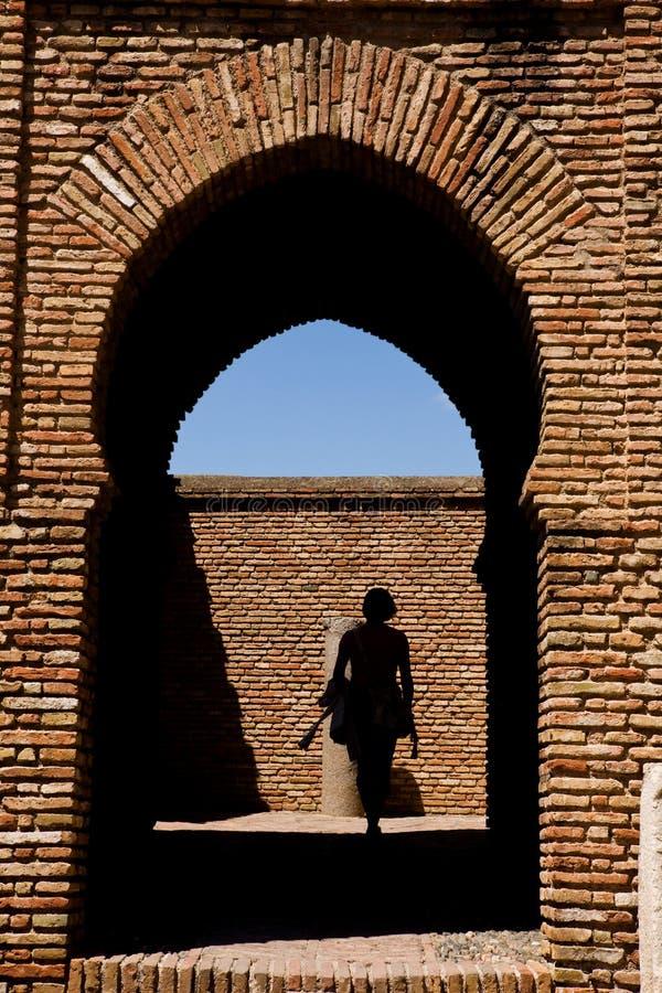 Mujer que pasa a través del Gateway en el castillo de Alcazaba imágenes de archivo libres de regalías