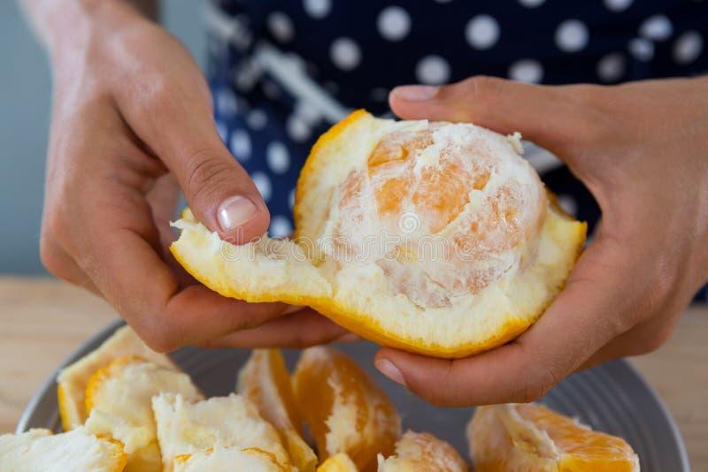 Mujer que pela la naranja imagen de archivo libre de regalías