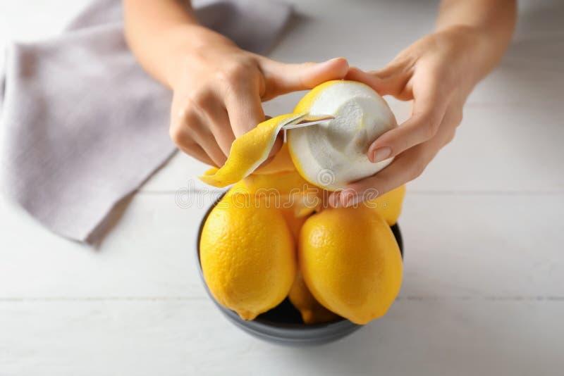 Mujer que pela los limones maduros en la tabla de madera blanca, primer imagenes de archivo