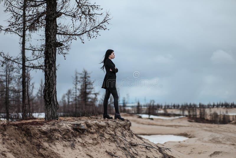 Mujer que permanece al borde de una colina de la arena foto de archivo libre de regalías