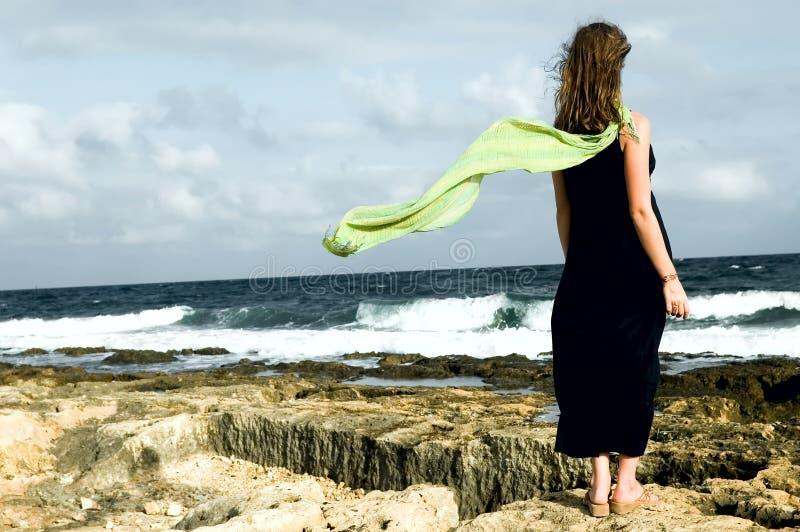 Mujer que permanece en la costa con el mantón detrás imagen de archivo libre de regalías